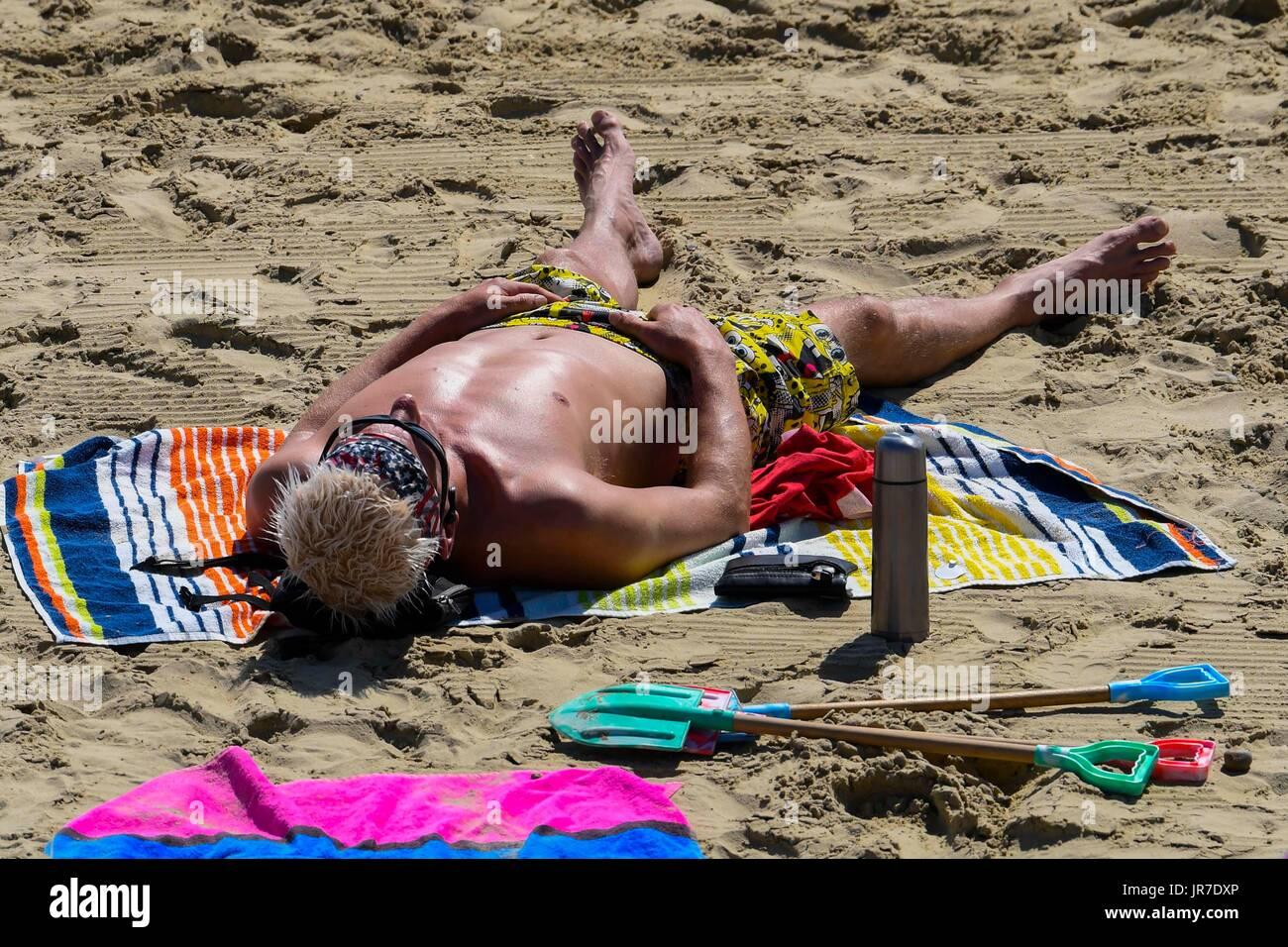 Lyme Regis, Dorset, UK. 4th August 2017.  UK Weather.   A sunbather on the beach enjoying the warm sunshine at the seaside resort of Lyme Regis in Dorset.  Photo Credit: Graham Hunt/Alamy Live News - Stock Image