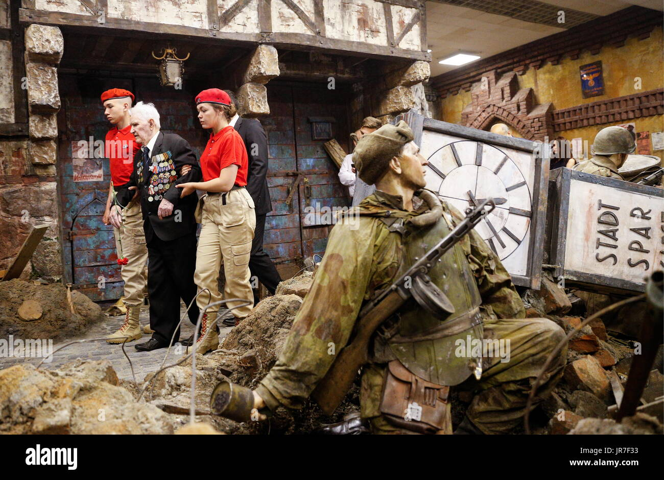 Kaliningrad Region, Russia. 3rd Aug, 2017. War veteran Ivan Tikhonov (2nd L) who took part in the final assault on Konigsberg in 1945, views a 3-dimensional panoramic exhibition titled 'Konigsberg 1945: the Final Assault' at the Kaliningrad Region Museum of History and Arts; the 360-degree display, which depicts the April 1945 assault by the Red Army on the city of Konigsberg in WWII, is an artwork by the Nevsky Batalist team led by Dmitry Poshtarenko. Credit: Vitaly Nevar/TASS/Alamy Live News - Stock Image