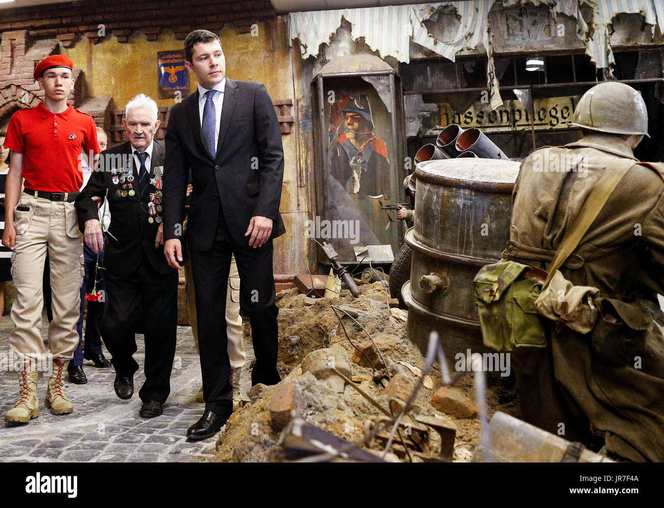 Kaliningrad Region, Russia. 3rd Aug, 2017. War veteran Ivan Tikhonov (2nd L) who took part in the final assault on Konigsberg in 1945, and the acting governor of Kaliningrad Region, Anton Alikhanov (R), view a 3-dimensional panoramic exhibition titled 'Konigsberg 1945: the Final Assault' at the Kaliningrad Region Museum of History and Arts; the 360-degree display, which depicts the April 1945 assault by the Red Army on the city of Konigsberg in WWII, is an artwork by the Nevsky Batalist team led by Dmitry Poshtarenko. Credit: Vitaly Nevar/TASS/Alamy Live News - Stock Image