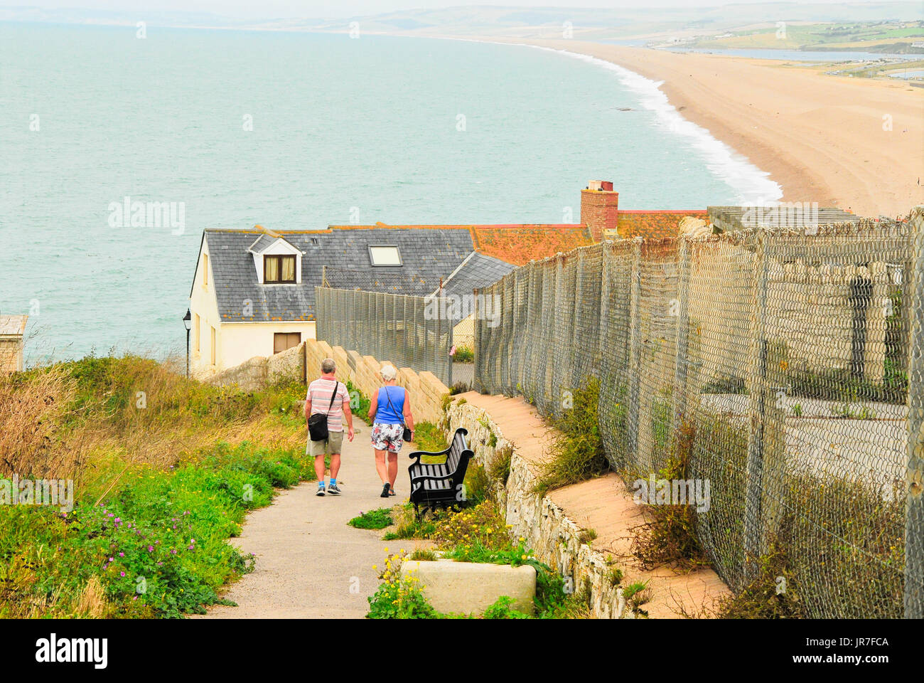 Chesil Beach, Dorset. 04th Aug, 2017. UK Weather: A couple on Portland walk down the steep path to Chesil Beach on a bright and breezy day in Dorset Credit: stuart fretwell/Alamy Live News - Stock Image