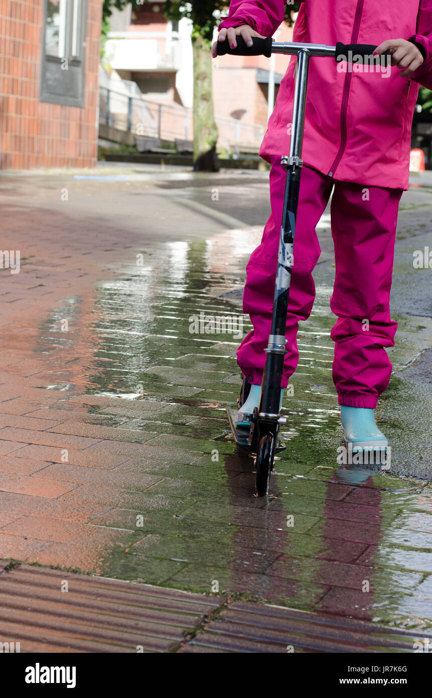Stockholm, Sweden. 4th Aug, 2017. Rainy day in Stockholm after several days with warm summer days without rain. Girl in colourful rain clothes and rubber boots rides her kick-bike in the rainy streets. Credit: Jari Juntunen/Alamy Live News - Stock Image