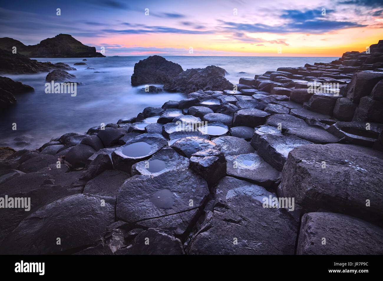 sunset over basalt rocks formation Giant's Causeway, Port Ganny Bay and Great Stookan, County Antrim, Northern - Stock Image