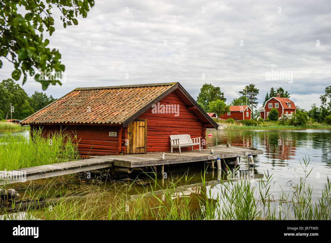The old timbered boathouse with the liars bench on the bridge in the northern part of Stockholm archipelago, Bjorko-Arholma, Marum - Stock Image
