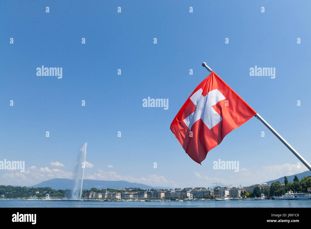 Flag of the flag of Switerland in the city center of Geneva, on the Leman lake. The iconic Jet d'Eau (Water Jet) can be seen in the background  Pictur - Stock Image