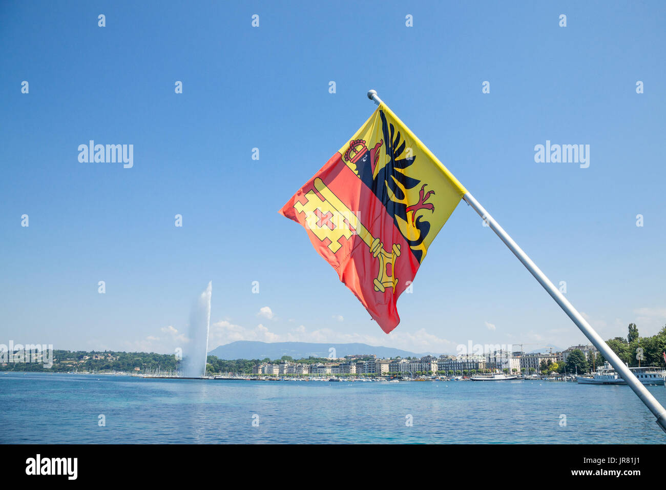 Flag of the Geneva Canton in the city center of Geneva, on the Leman lake. The iconic Jet d'Eau (Water Jet) can be seen in the background  Picture of  - Stock Image