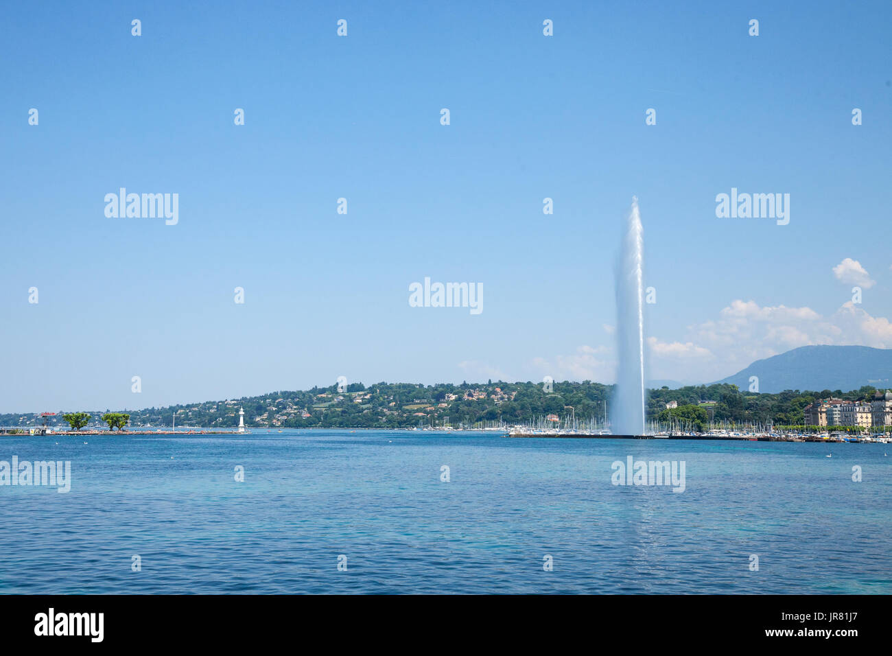 Geneva's main monument and landmark, the Jet d'Eau (Water Jet), taken in a summer afternoon with a blue sky. Geneva is one of the biggest financial pl - Stock Image