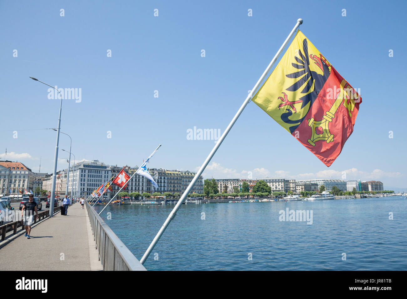 Flag of the Geneva Canton and flag of Switerland in the city center of Geneva on the Mont Blanc Bridge (Pont du Mont Blanc), on the Leman lake  Pictur - Stock Image
