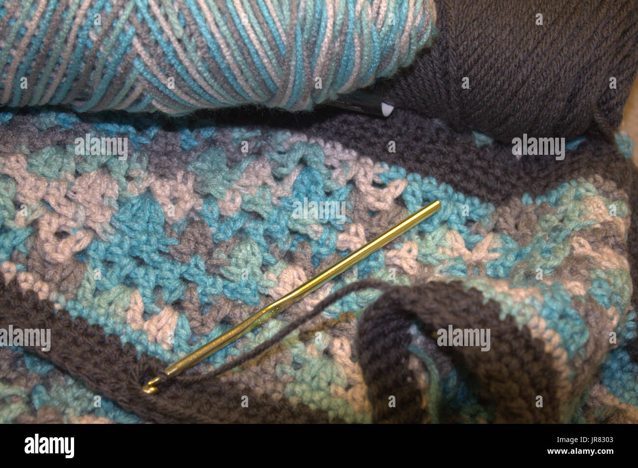 Crochet in blues and grays, with crochet needle. - Stock Image