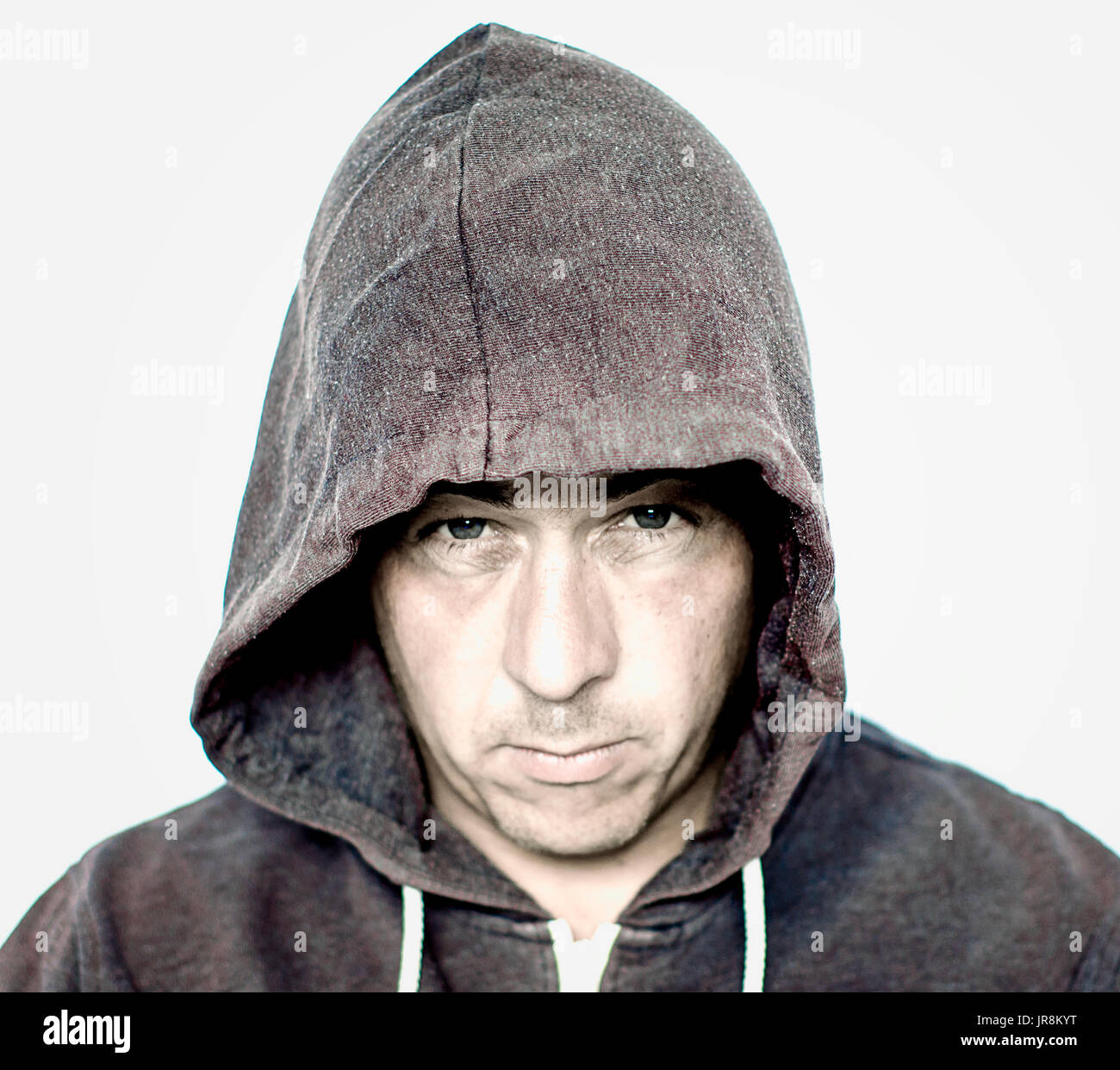 Man with a mean and moody face wearing a grey hooded top with intentional grain and a grunge look - Stock Image