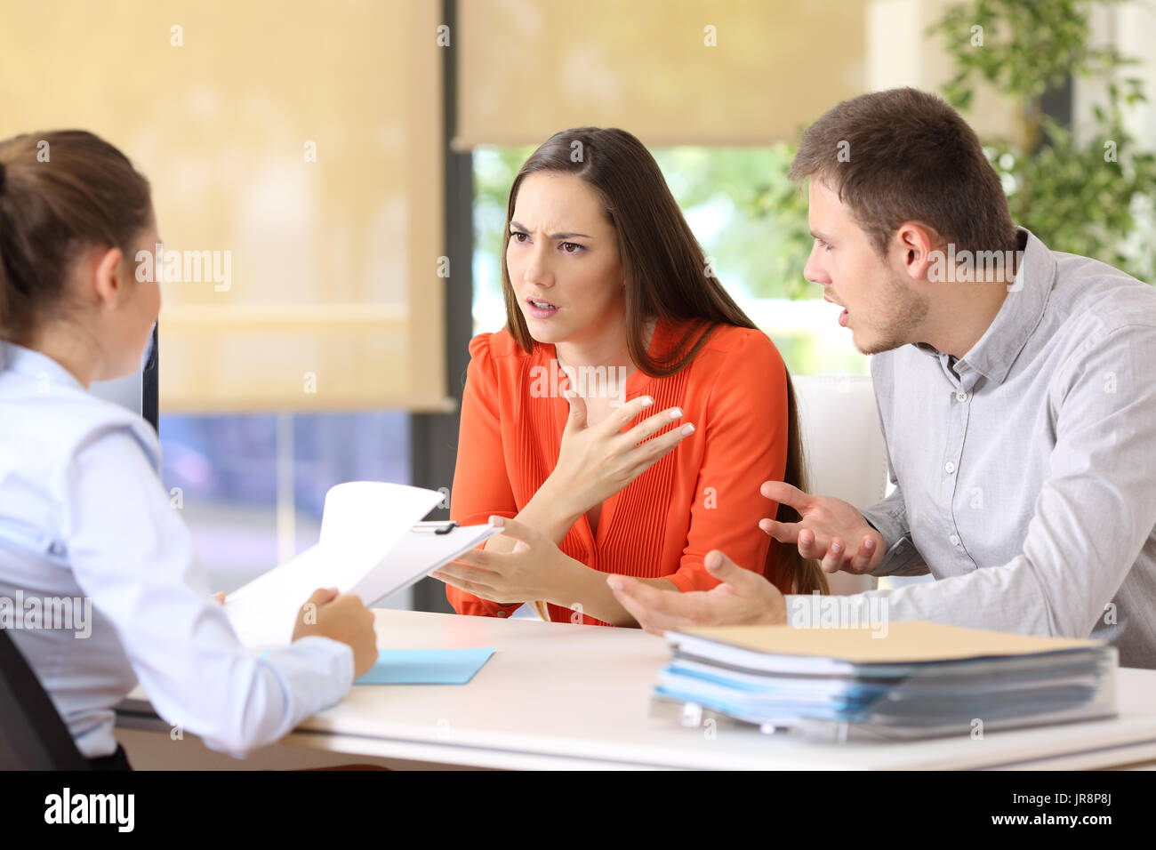 Angry couple arguing telling their problems sitting in a desktop of a marriage counseling or office - Stock Image