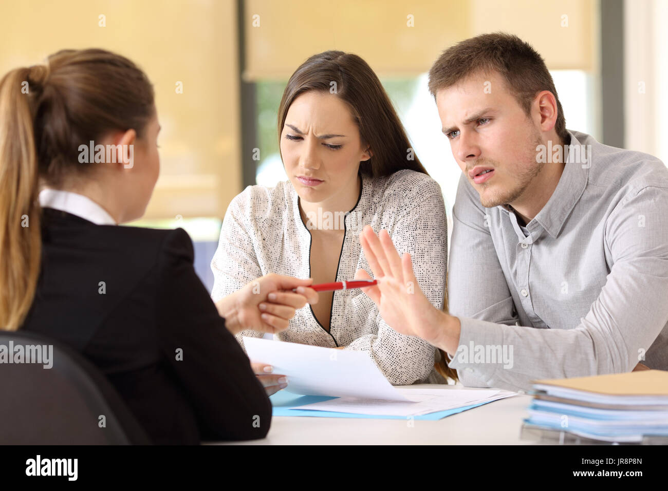 Saleswoman offering a pen to a couple of angry customers that rejects to sing a contract at office - Stock Image