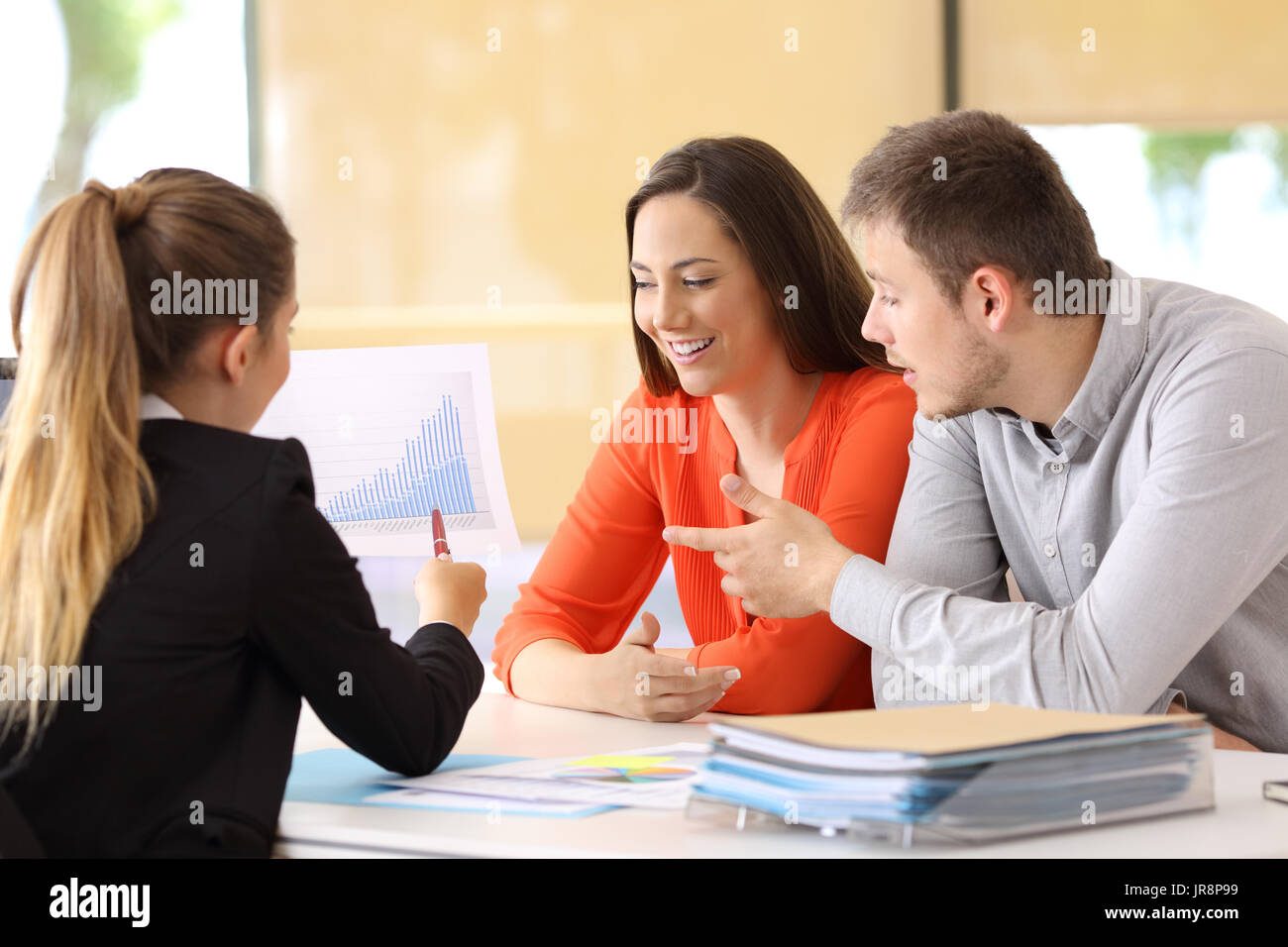 Three partners checking and commenting a growth graph at office - Stock Image