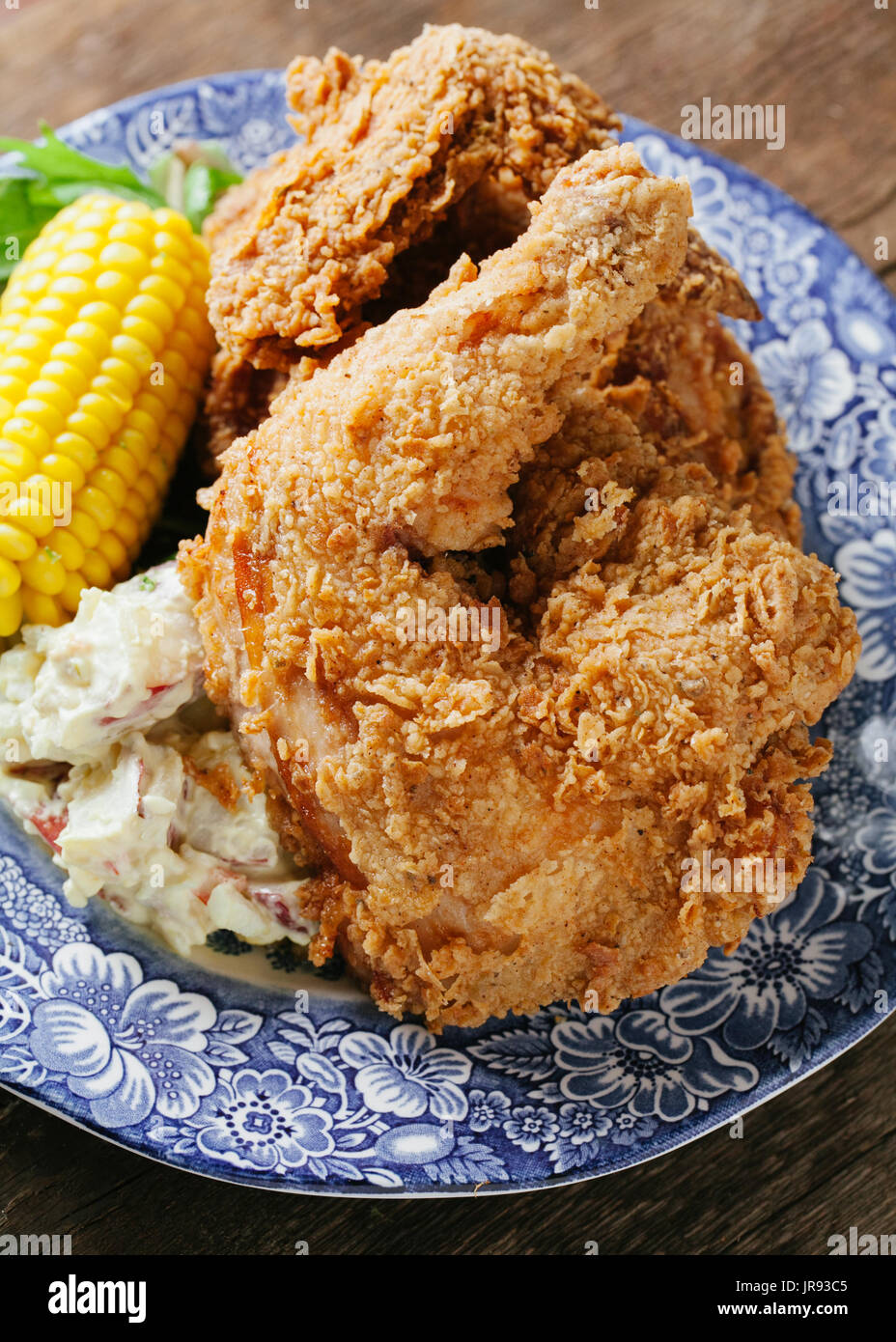 Buttermilk fried chicken with corn and potato salad on a blue plate - Stock Image