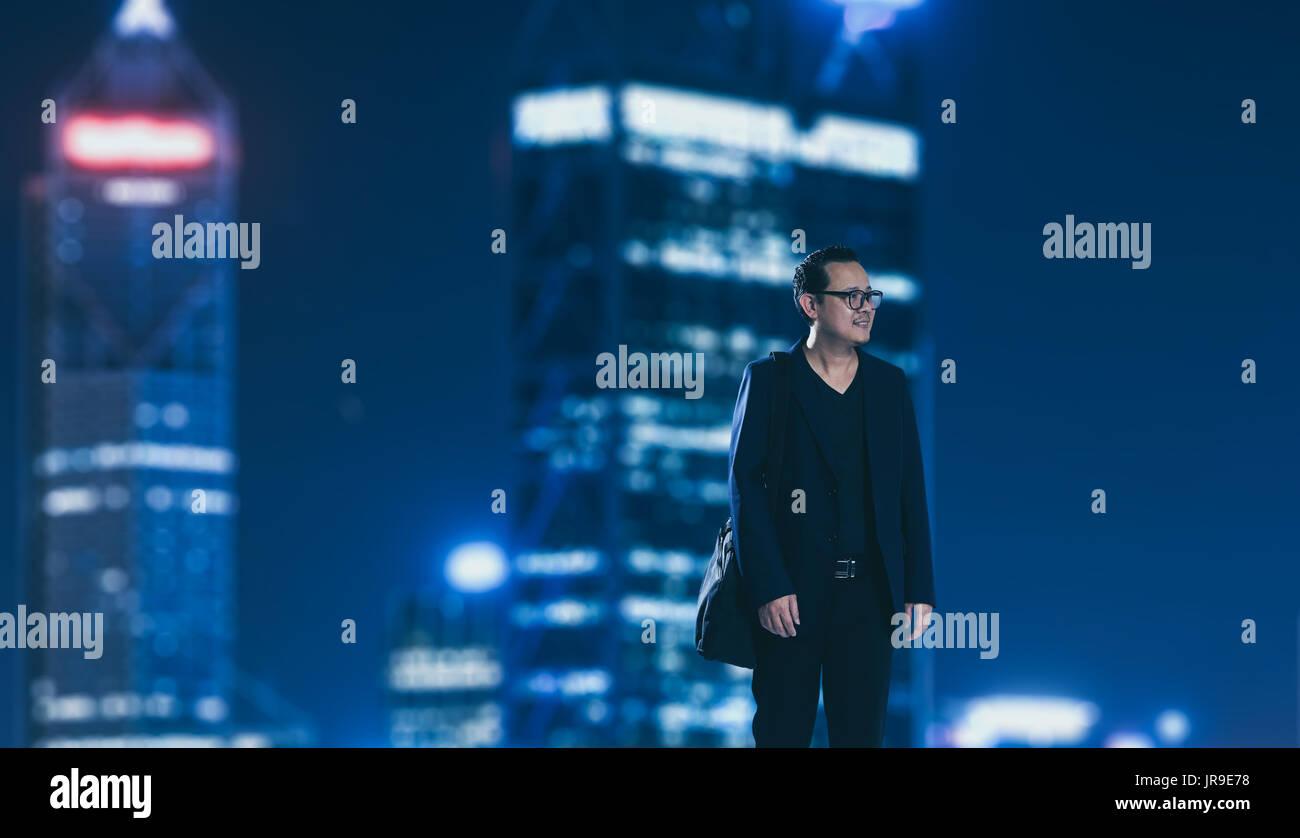 Young businessman standing with out of focus city skyscraper background . Night scene. - Stock Image