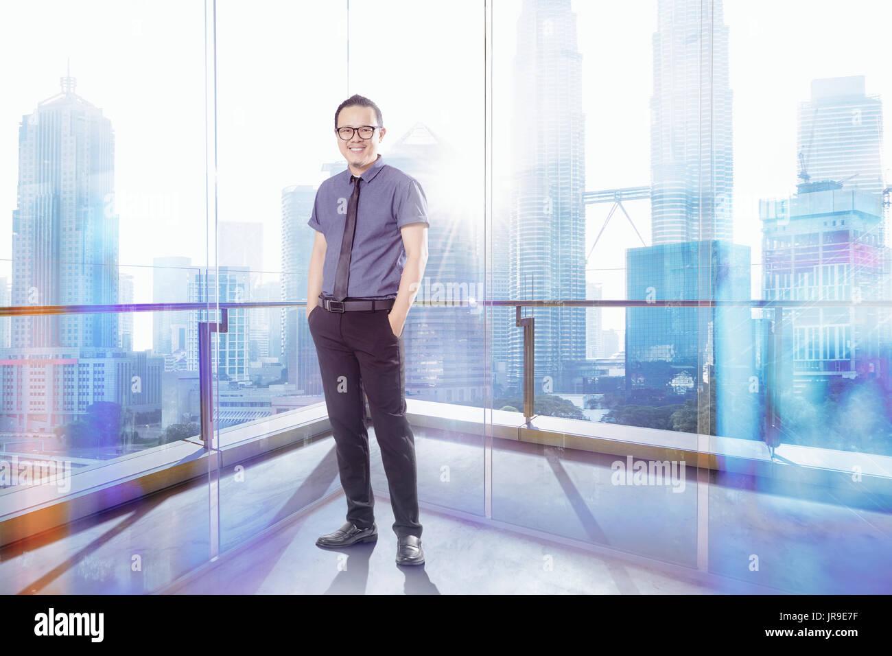 Full length portrait of happy 30s 40s Asian businessman . - Stock Image
