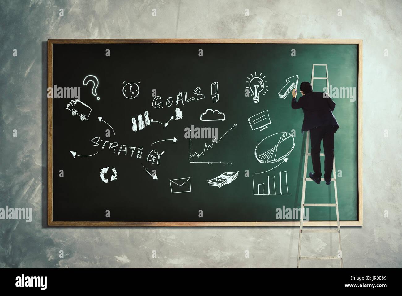 Men drawing development graph strategy on blackboard . - Stock Image