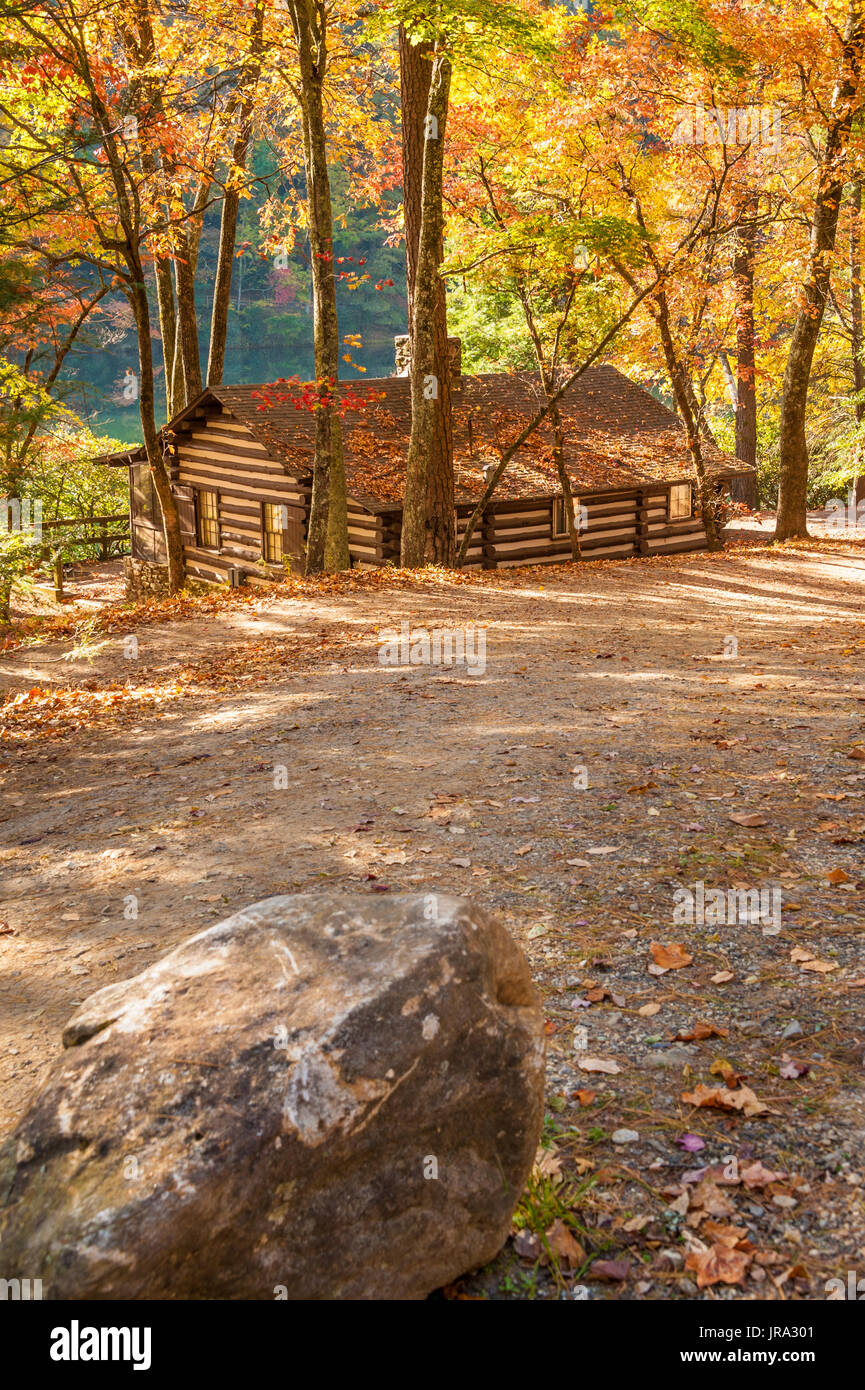 Charming lakefront log cabin (built by the Civilian Conservation Corps in the 1930s) under a colorful spectrum of Autumn leaves at Vogel State Park. - Stock Image