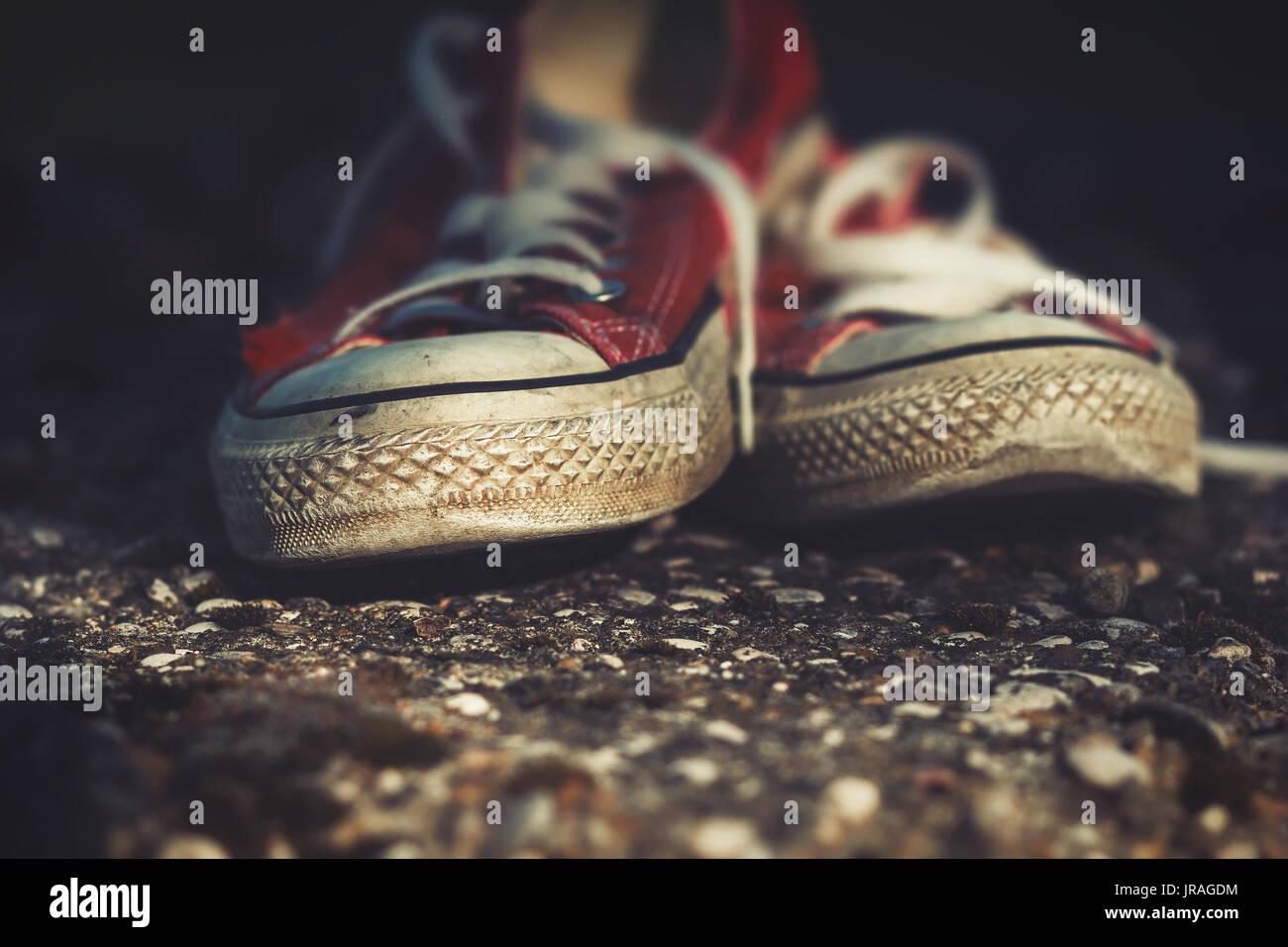 Old, worn out, red canvas sneakers on a concrete path - Stock Image