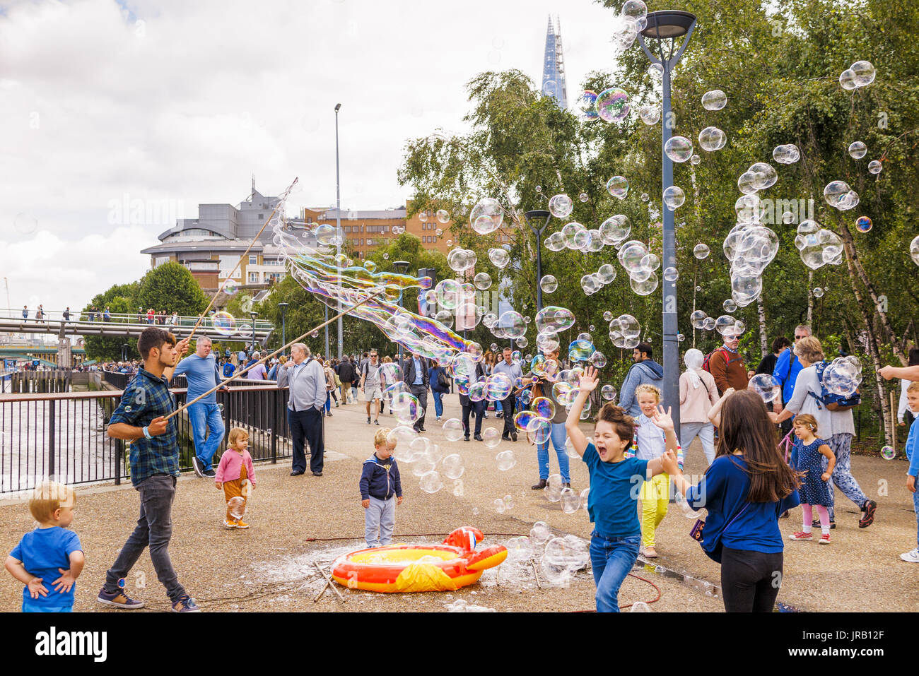 Street entertainer soliciting tips entertaining children by blowing large colourful bubbles, Bankside, Embankment, South Bank, London SE1, UK - Stock Image
