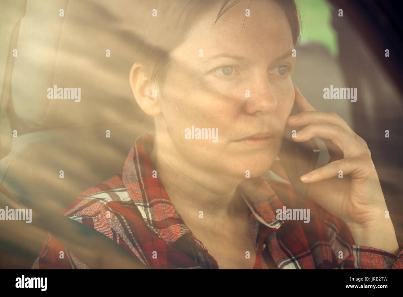 Worried woman talking on mobile phone in car, concerned adult caucasian female person during telephone conversation - Stock Image