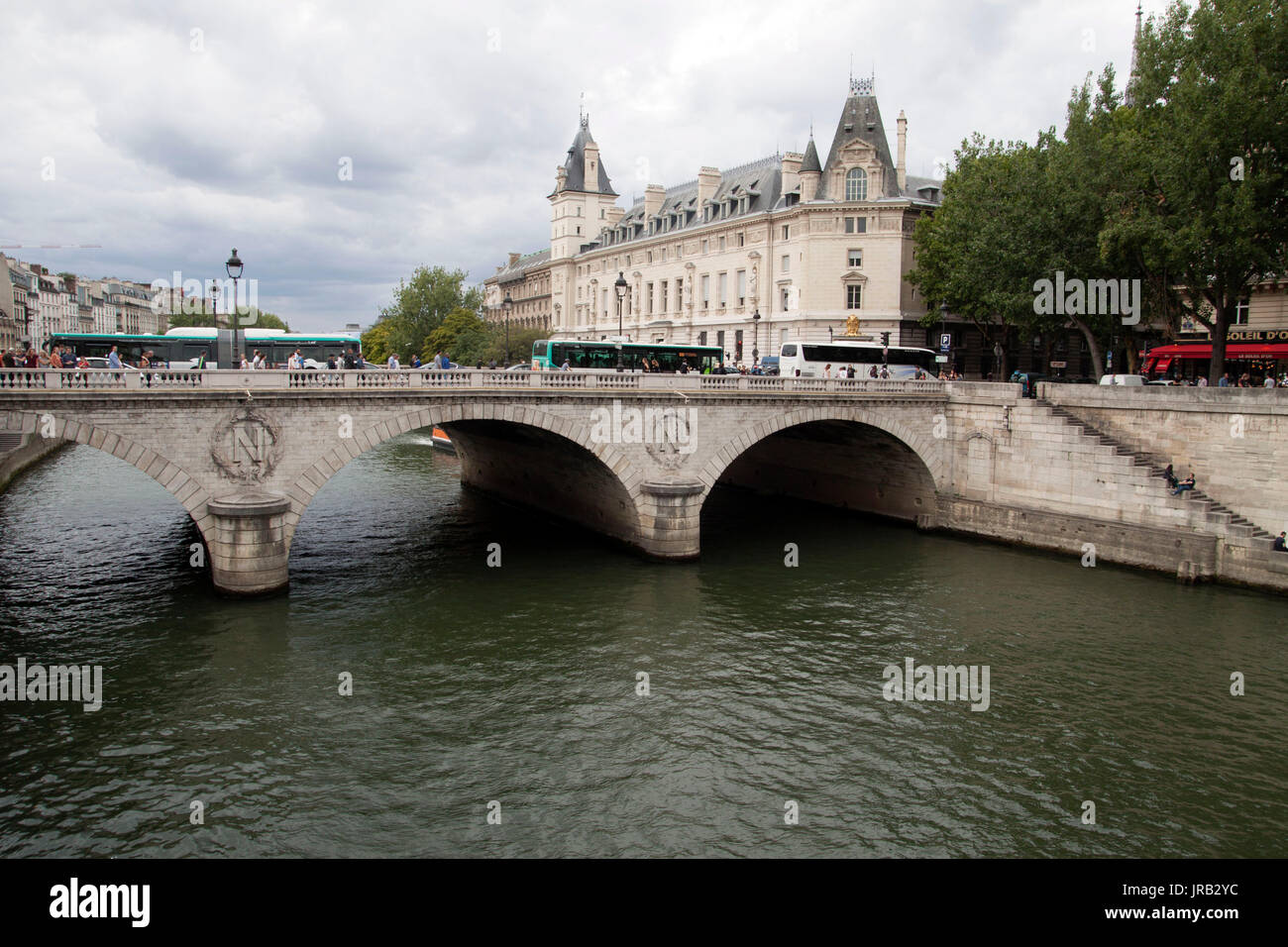 PARIJS , FRANKRIJK - JULY 23 ,2017:Old stone bridge with round bends over the river seine in paris. Around the bridge, tourists and buses travel - Stock Image