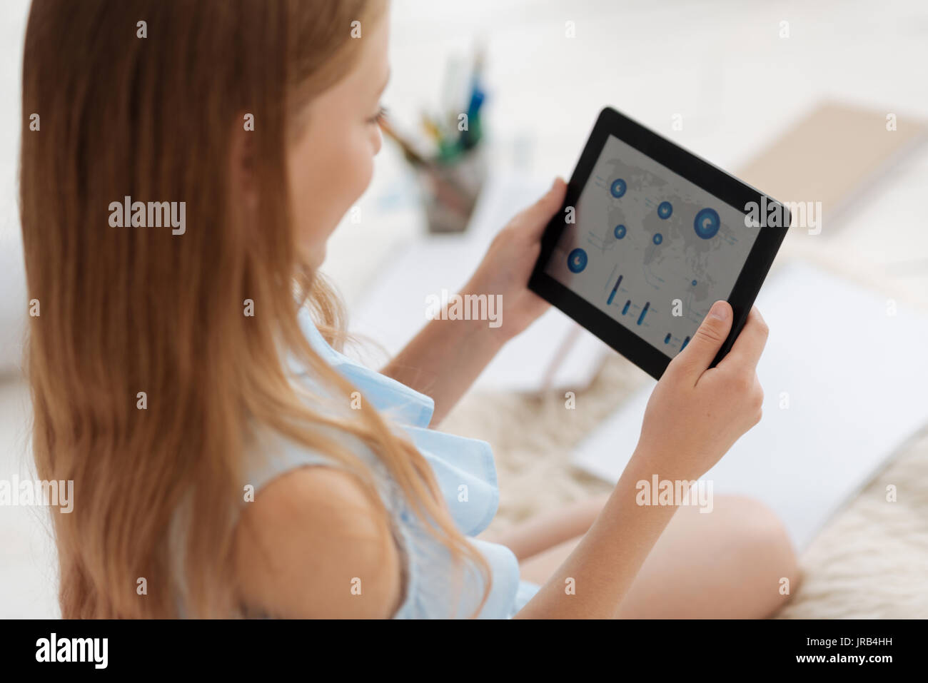 Smart female youngster looking at maps on tablet computer - Stock Image