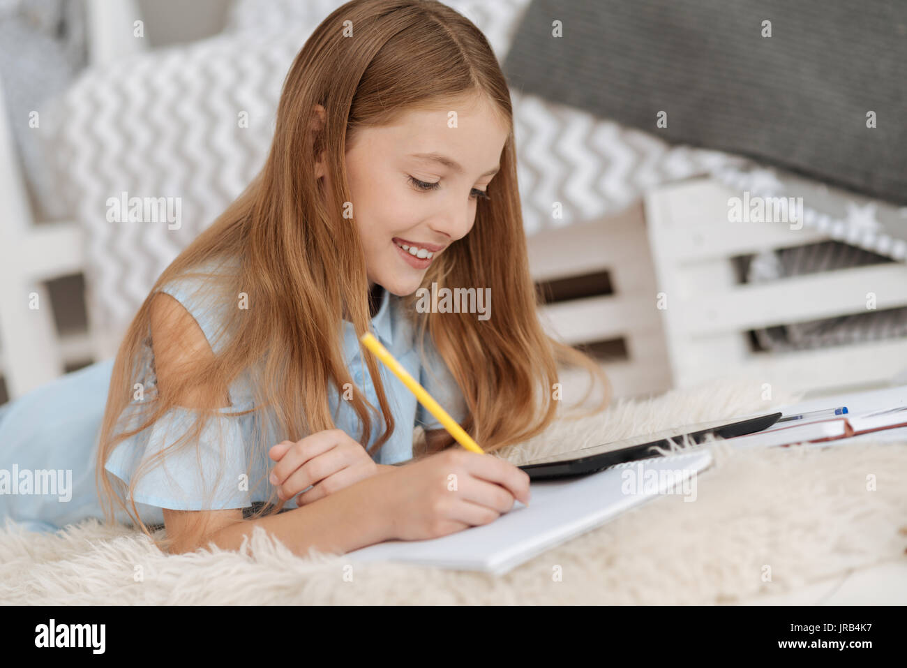 Adorable kid writing in notebook while studying at home - Stock Image