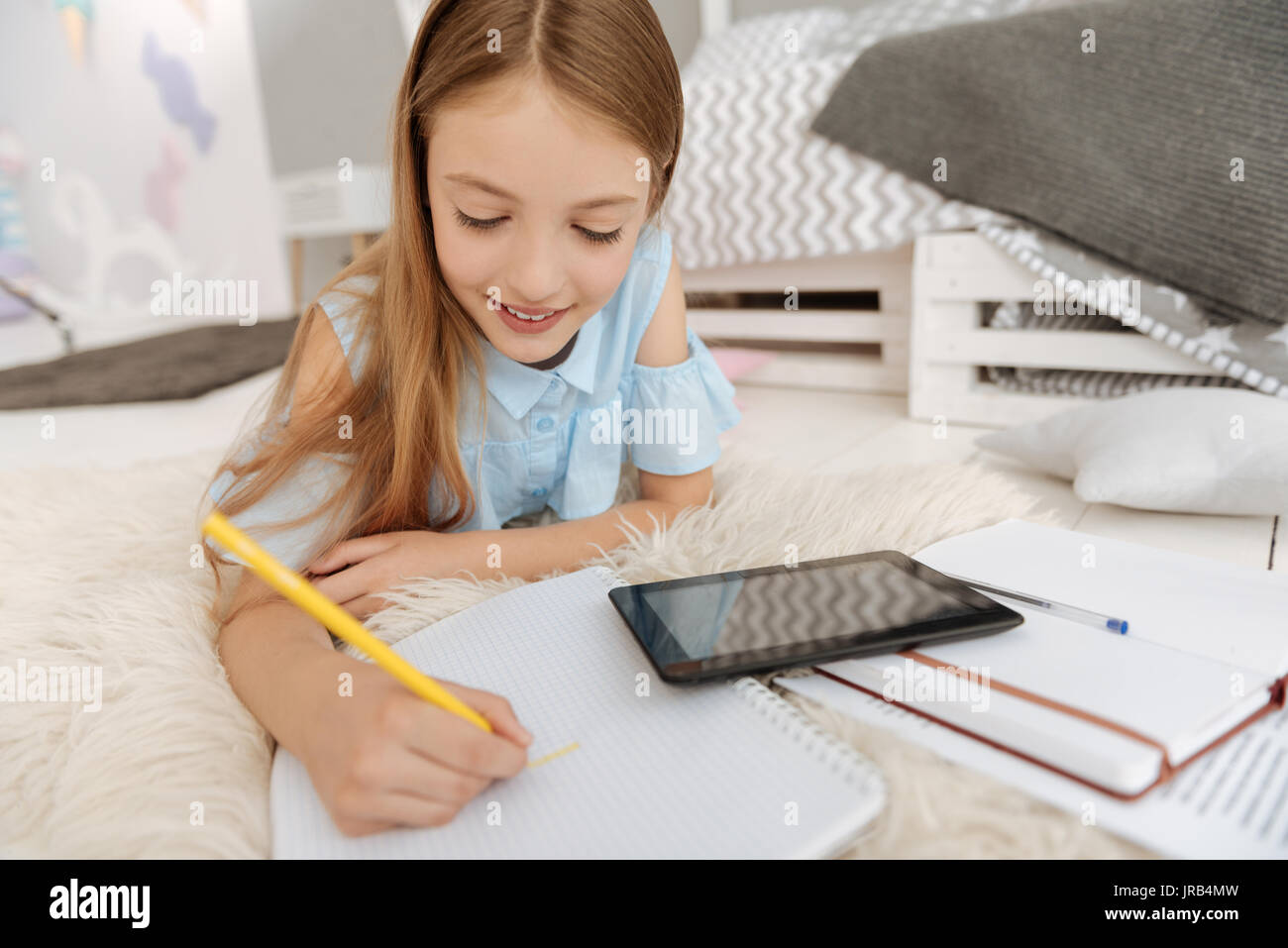 Cute little lady drawing in notebook - Stock Image