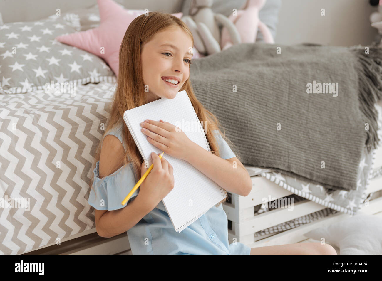Radiant girl embracing notebook while drawing - Stock Image