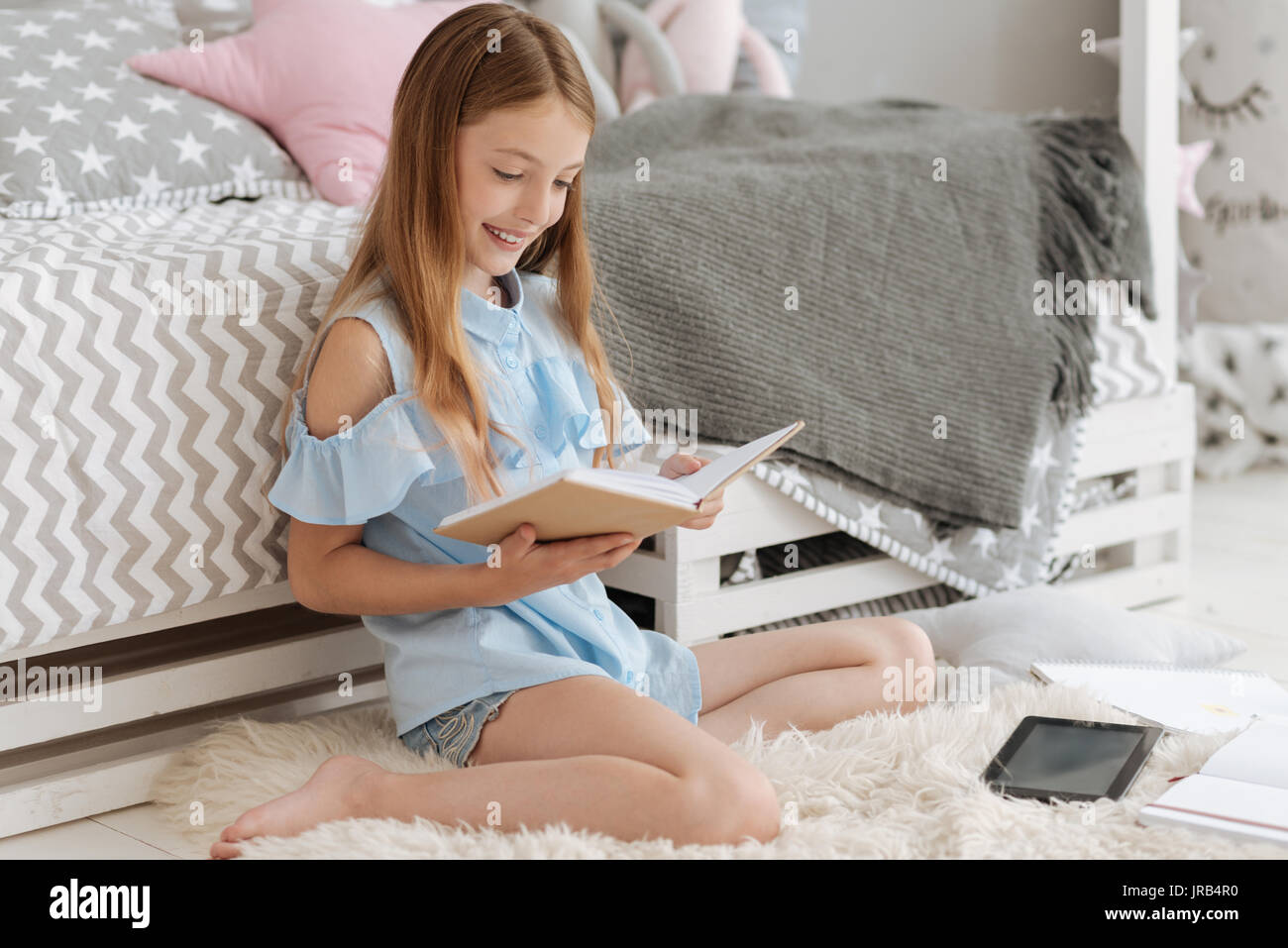 Happy girl smiling while reading book - Stock Image