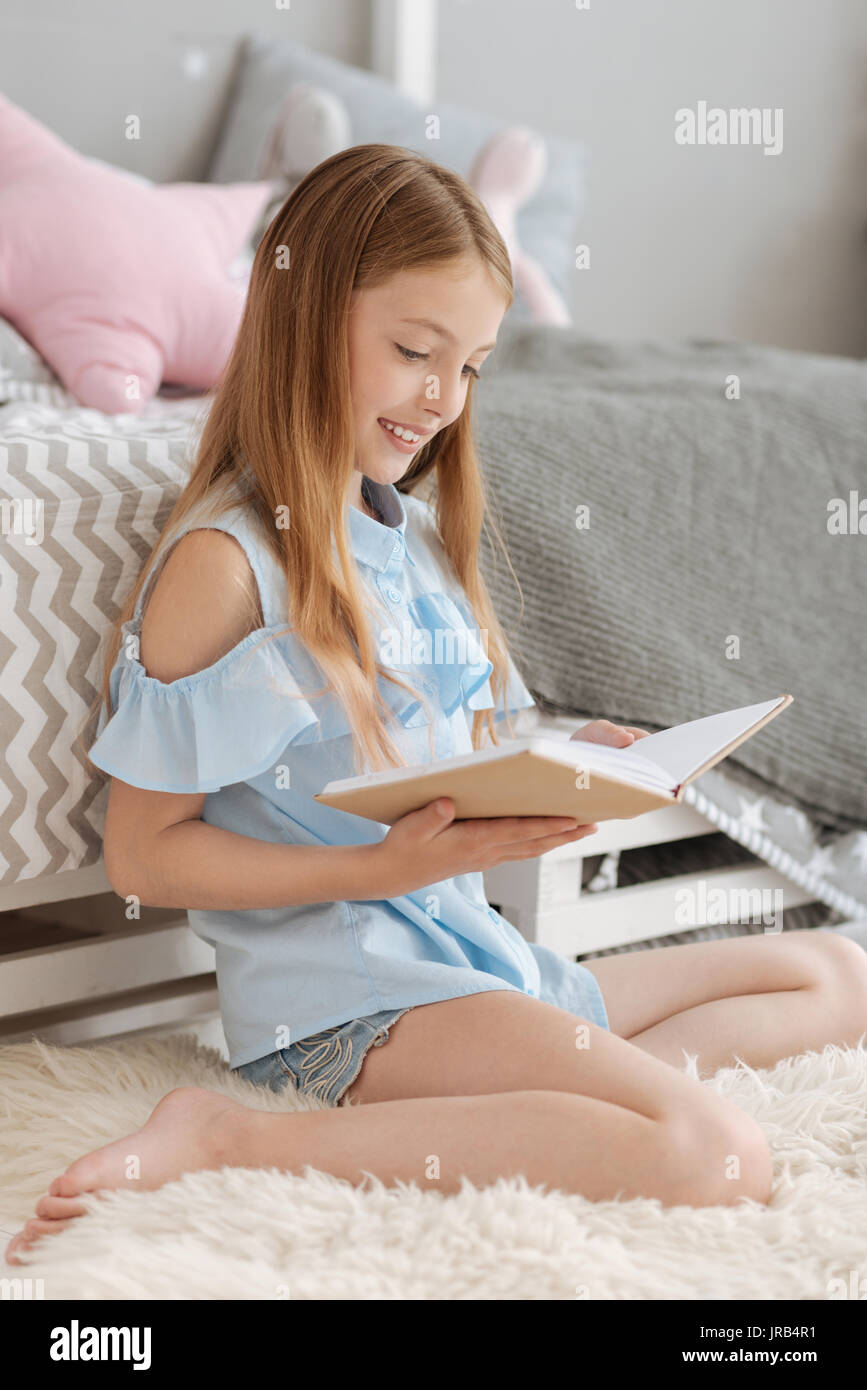 Smart young lady reading in bedroom - Stock Image