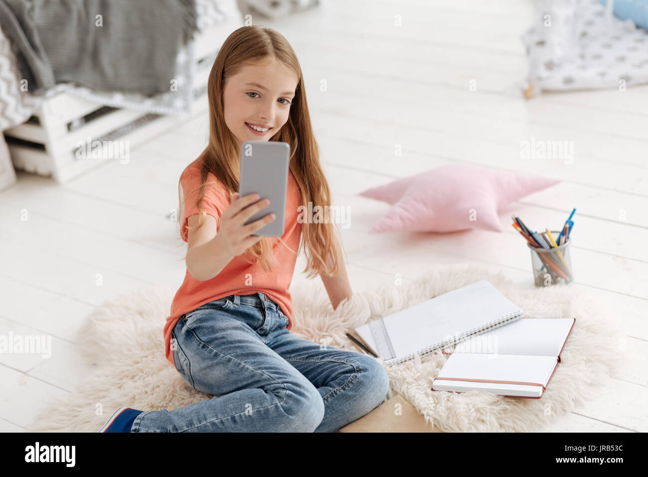 Cute schoolgirl in casual taking selfies - Stock Image