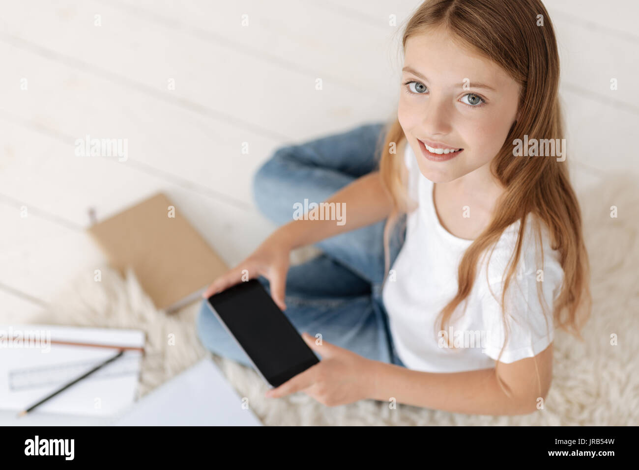 Diligent female pupil looking into camera while holding phone - Stock Image