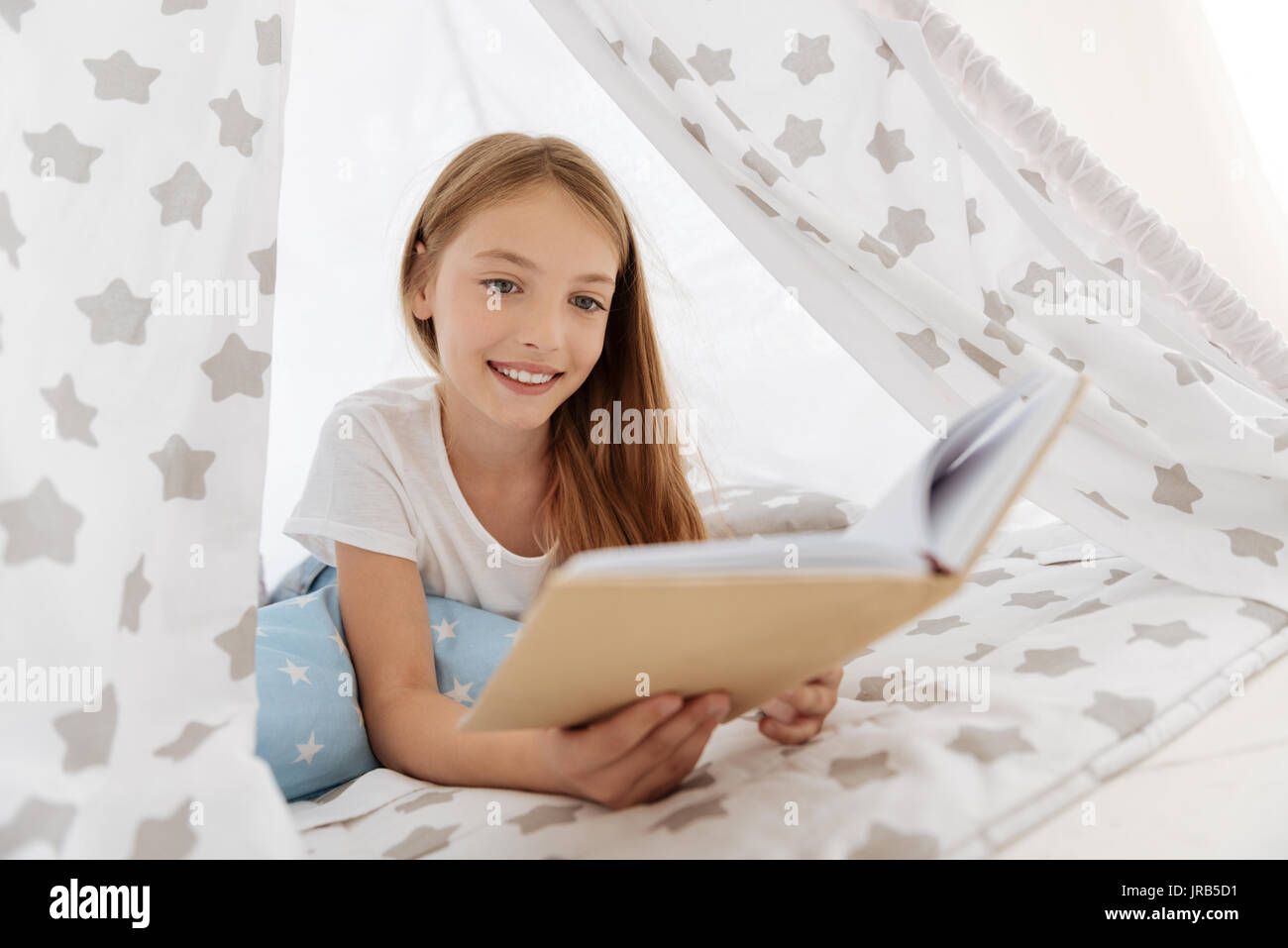 Smart young lady reading book in tent - Stock Image