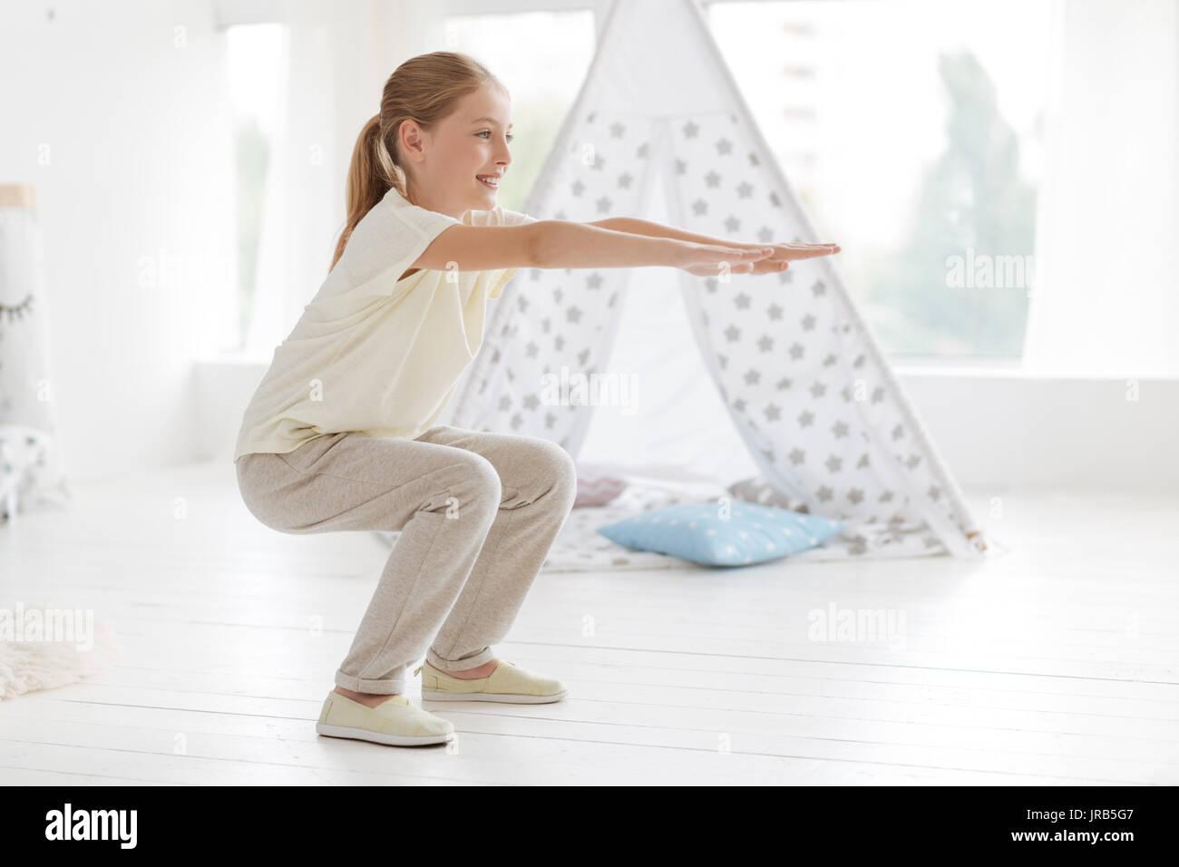 Athletics schoolgirl doing knee bends at home Stock Photo