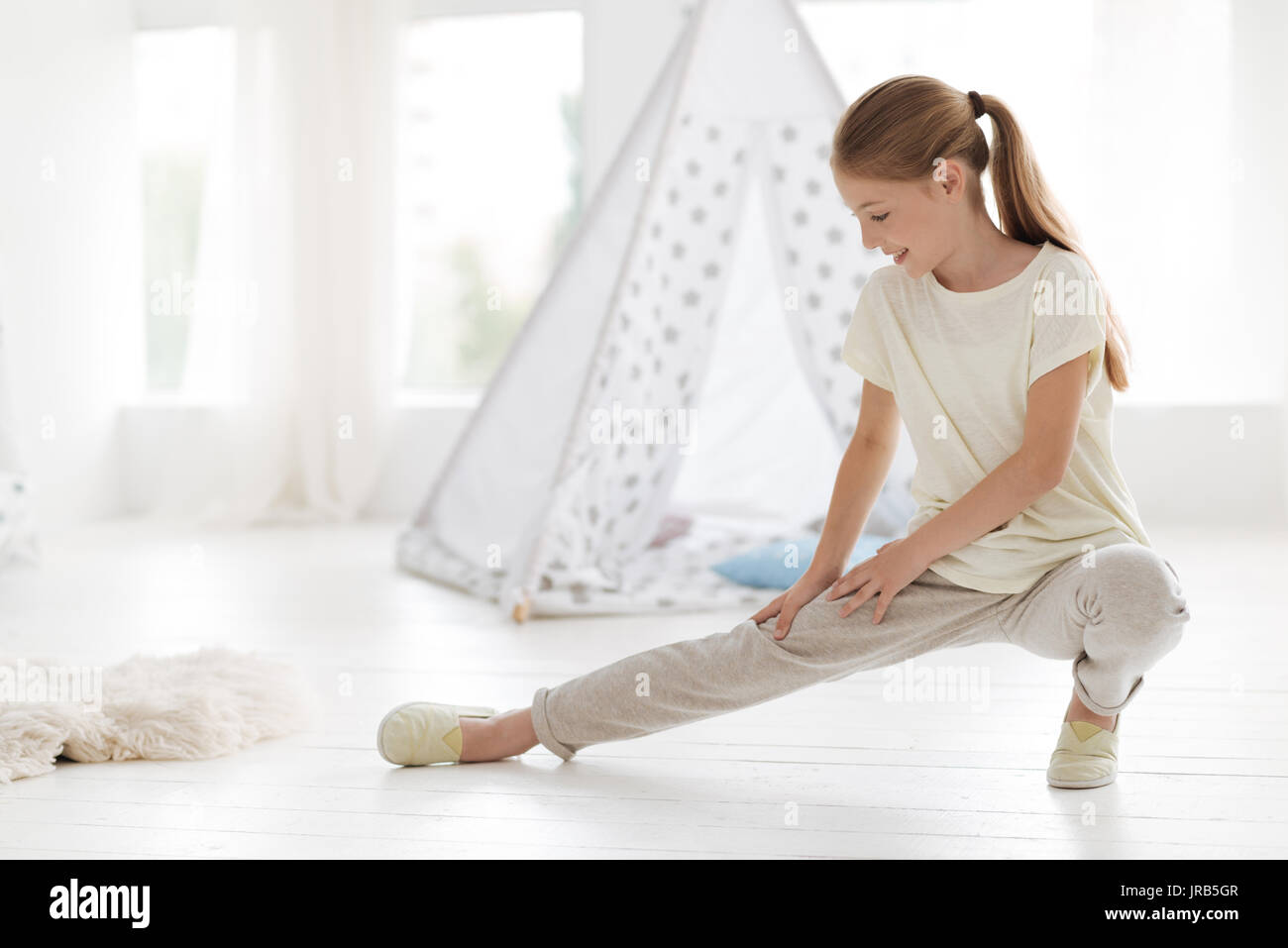 Focused girl doing warm up activities - Stock Image