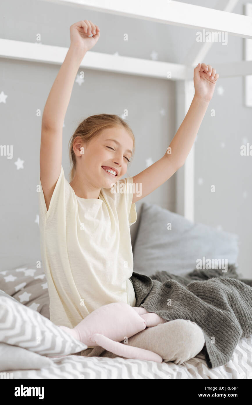 Excited child sitting on bed with hands in air - Stock Image