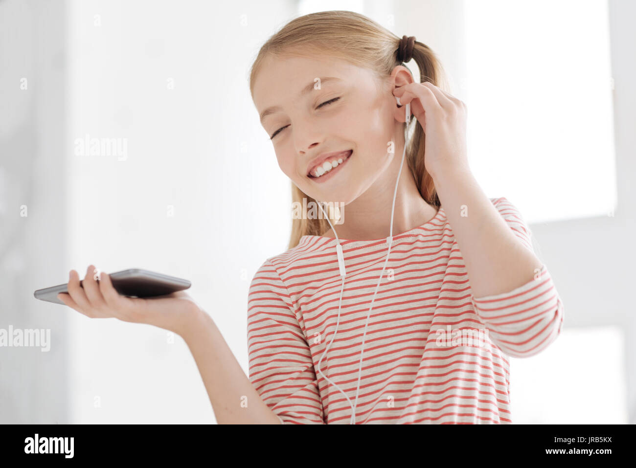 Cute little girl listening to her favorite music album - Stock Image
