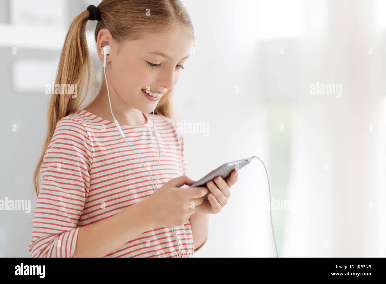Positive minded child listening to music - Stock Image