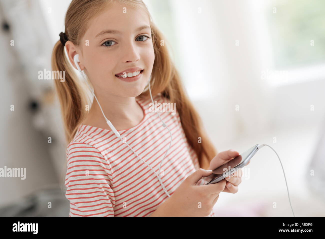 Cute girl with ponytails listening to music - Stock Image
