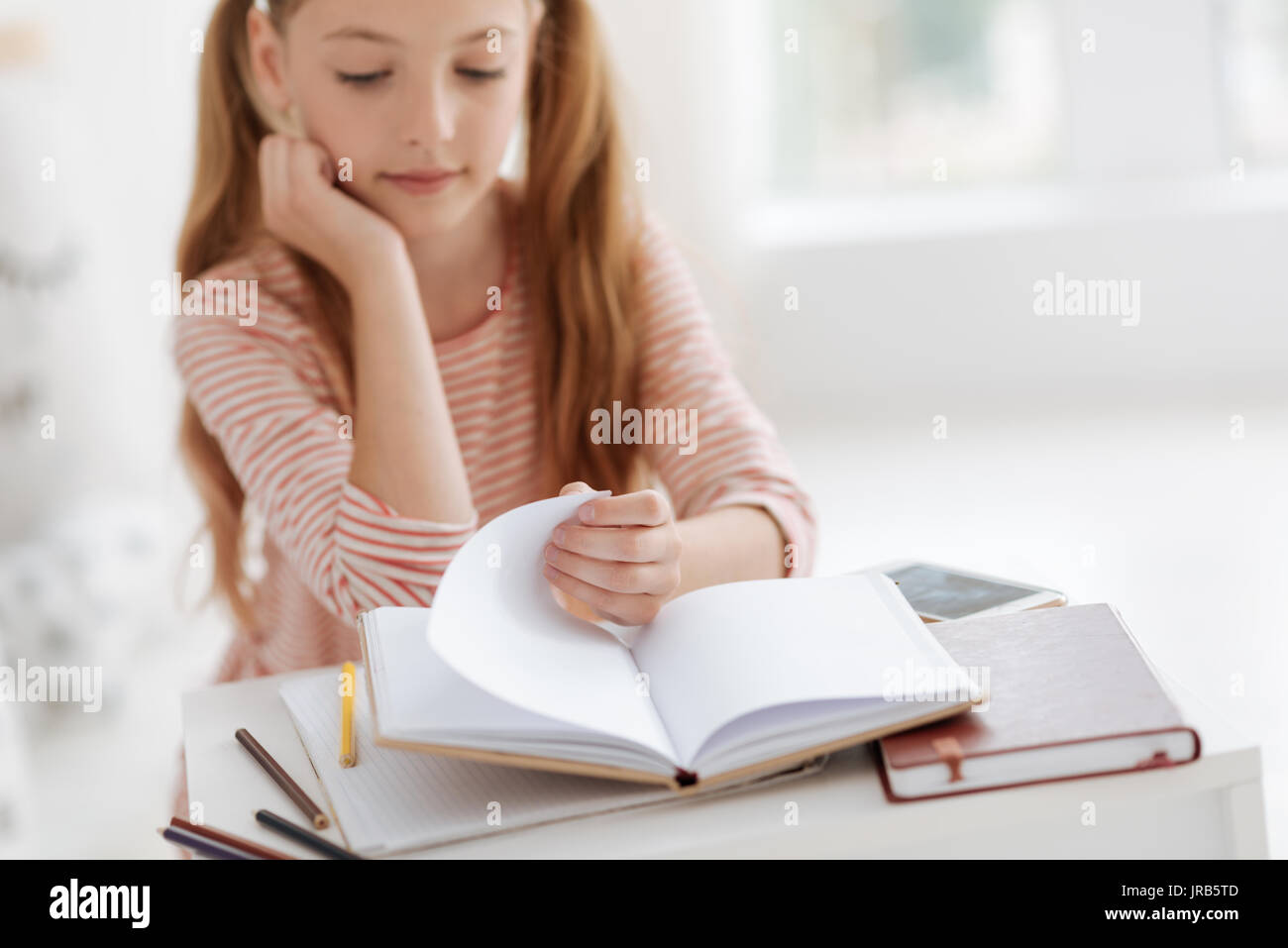 Intelligent little lady turning over pages of book - Stock Image