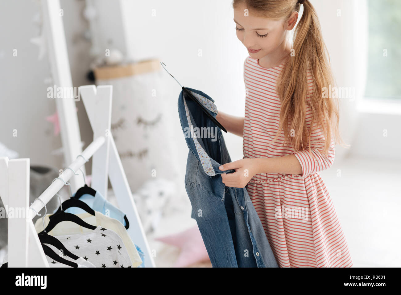 Young lady looking at denim shirt while choosing outfit - Stock Image