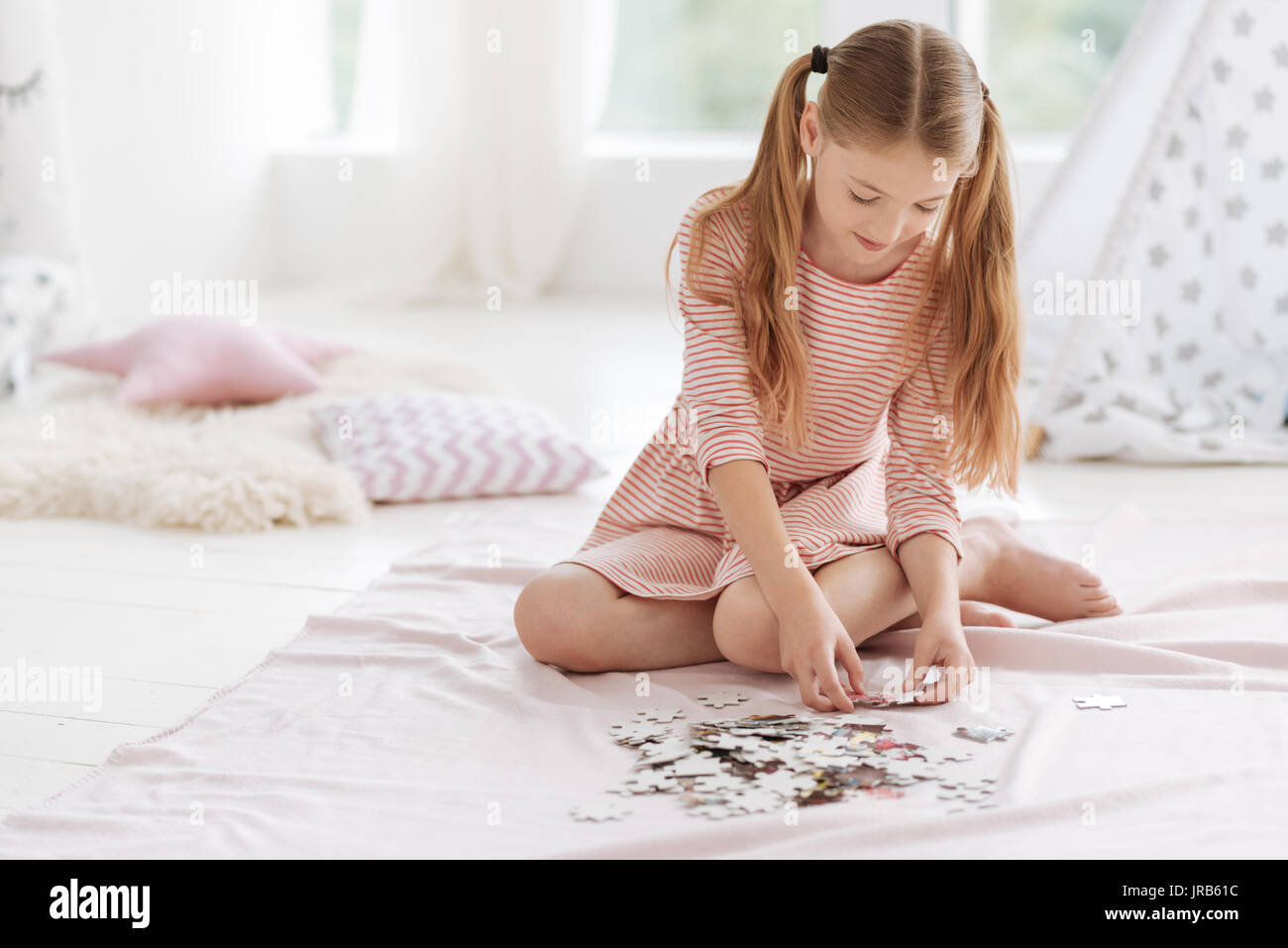 Well mannered kid playing puzzle game - Stock Image