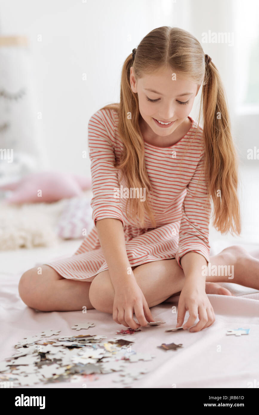 Radiant young lady enjoying puzzle game - Stock Image