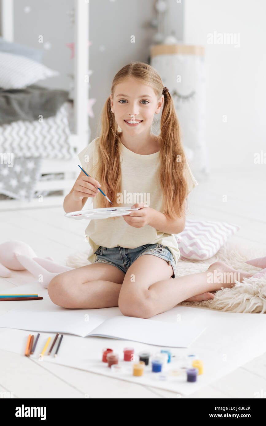 Smiling girl holding palette and smiling into camera - Stock Image