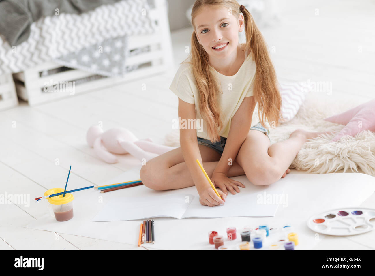 Beautiful girl looking into camera while drawing - Stock Image