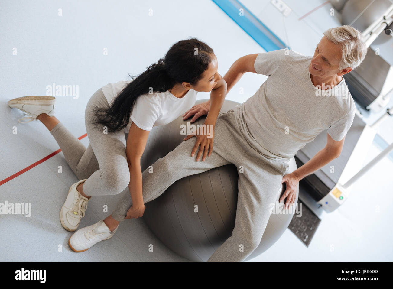Competent coach doing massage for injured leg - Stock Image