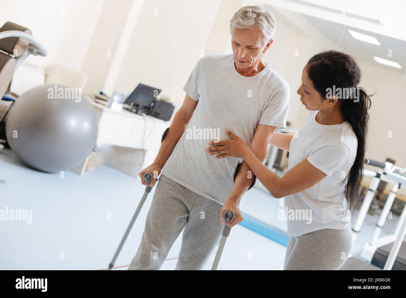 Concentrated grey-haired man bowing head - Stock Image