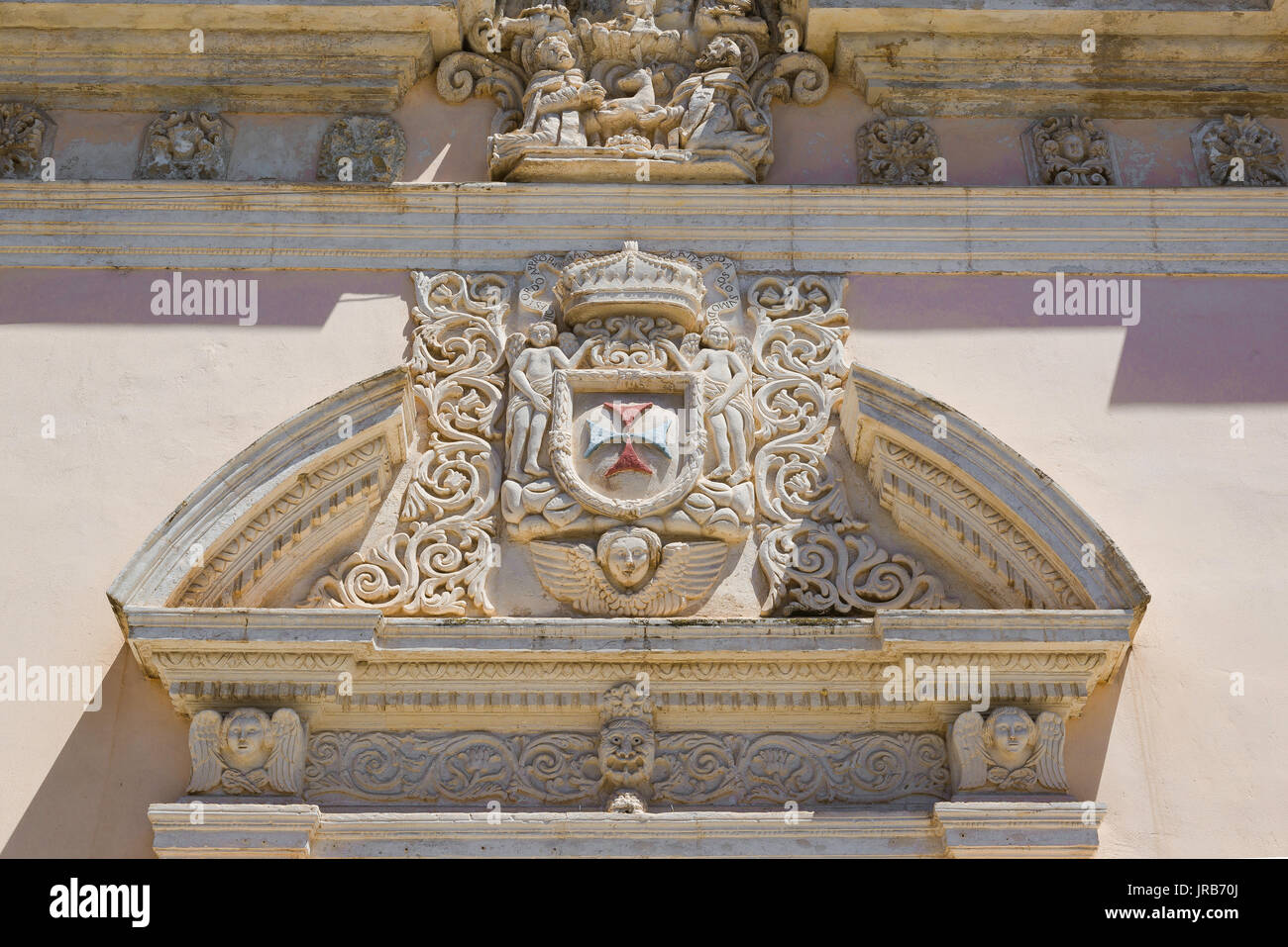 Baroque broken pediment sited above the west door of the Chiesa della S. Trinita church in Sassari, Sardinia. Stock Photo