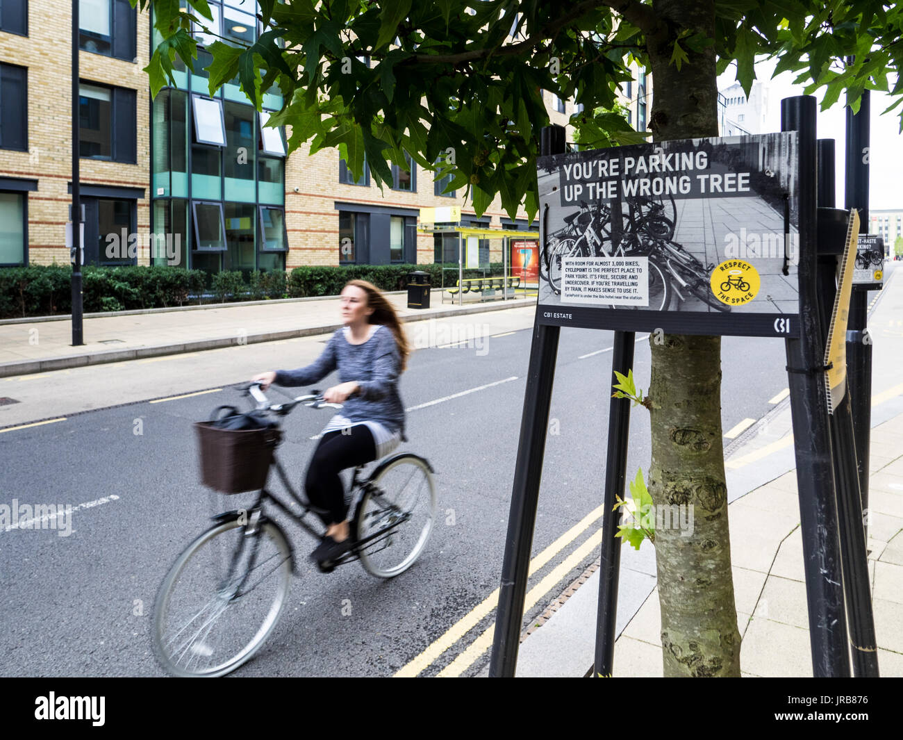 Cambridge bike congestion - Cyclists pass signs asking people not to attach bikes to street furniture, following the opening of a nearby cycle park - Stock Image
